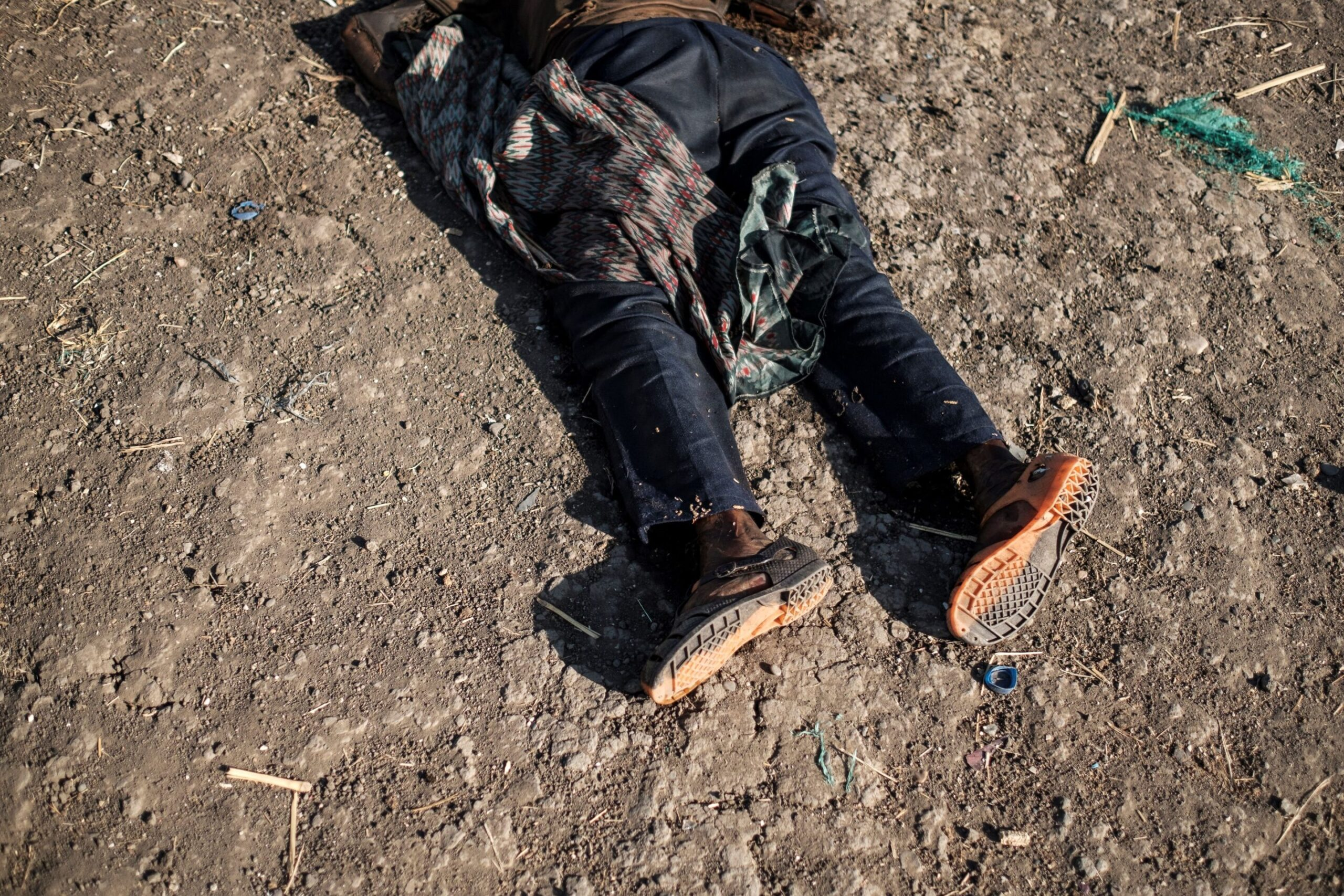 """EDITORS NOTE: Graphic content / This photograph taken on November 21, 2020, shows the body of an alleged victim of the November 9, 2020  massacre laying in a road in the outskirts of Mai Kadra, Ethiopia. - A local youth group aided by police and militia killed at least 600 people in a """"rampage"""" during the first week of fighting in Ethiopia's northern Tigray region, the national rights watchdog said on November 24, 2020. The massacre in the town of Mai-Kadra is the worst-known attack on civilians during Ethiopia's ongoing internal conflict pitting federal forces against leaders of Tigray's ruling party, the Tigray People's Liberation Front (TPLF). Some Tigrayan refugees from Mai-Kadra who have fled across the border to Sudan blame government forces for killings there. Amnesty International previously reported that """"scores, and likely hundreds, of people were stabbed or hacked to death"""" in the November 9 attack in Mai-Kadra. But November 24, 2020's report from the Ethiopian Human Rights Commission (EHRC) provides a more detailed account, accusing the Tigrayan youth group known as """"Samri"""" of targeting non-Tigrayan seasonal labourers working on sesame and sorghum farms in the area. The EHRC is a government-affiliated but independent body whose chief commissioner, Daniel Bekele, was appointed by Prime Minister Abiy Ahmed. (Photo by EDUARDO SOTERAS / AFP) (Photo by EDUARDO SOTERAS/AFP via Getty Images)"""